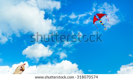 Hand holding kite in the cloudy sky. Focus to the kite - stock photo