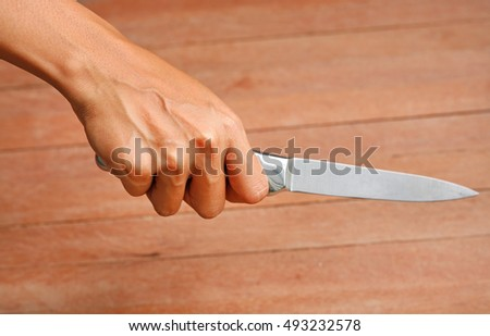 hand holding knife against plank wood