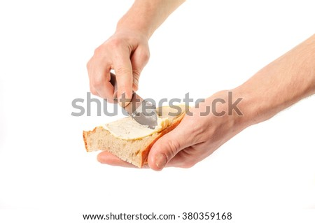 Hand holding knife spreading butter on bread.