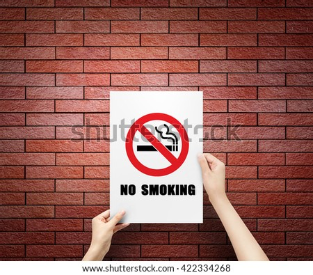 hand holding label paper no smoking at wall