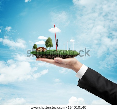 hand holding landscape with eco wind turbine, and climbing businessman - stock photo