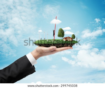 hand holding landscape with eco wind turbine and climbing businessman