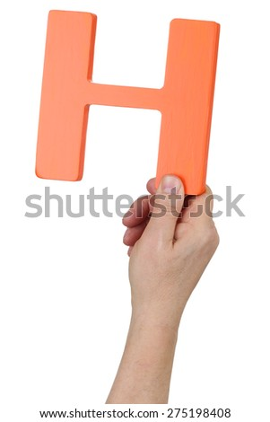 Hand holding letter H from alphabet isolated on a white background - stock photo