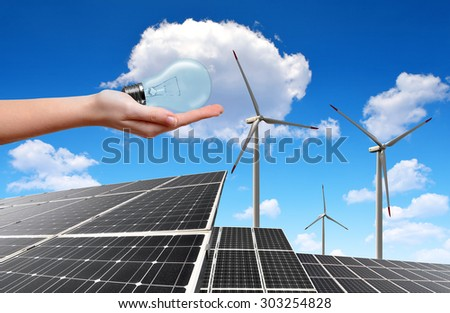 Hand holding lightbulb in the background solar energy panels and wind turbines
