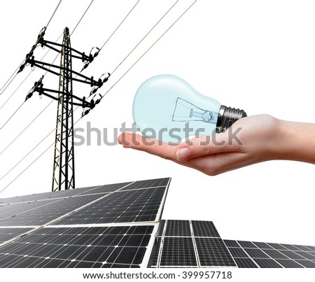 Hand holding lightbulb. In the background solar panel and high voltage tower. Clean energy concept. - stock photo