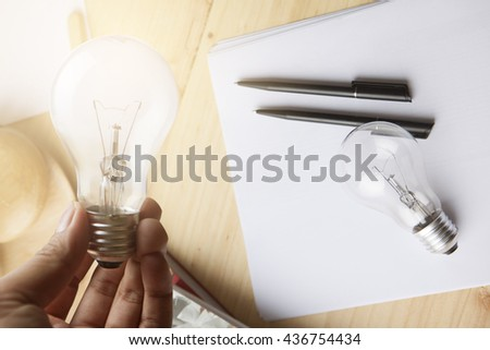 Hand holding lighting bulb with blank paper and pen on wooden table and soft flare filter - stock photo