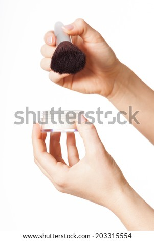 Hand holding loose powder and a brush - stock photo