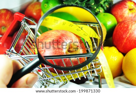 Hand holding magnifier focused on healthy food - stock photo