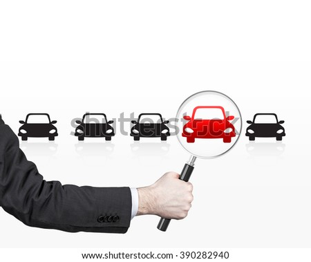 Hand holding magnifier over red picture of car in row of black cars. Front view. White background. Concept of choice. - stock photo