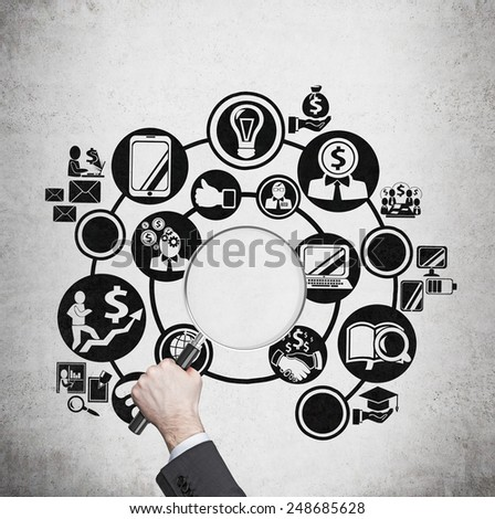 hand holding magnifier with business symbols - stock photo