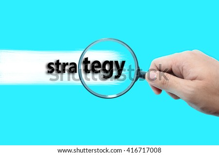 Hand holding magnifying glass focusing on the words Strategy against turquoise background.