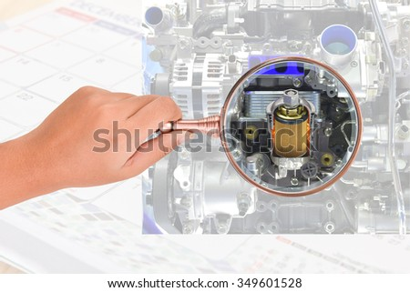Hand holding magnifying glass isolated on Oil filter car engine check periodicaly. This has clipping path. - stock photo