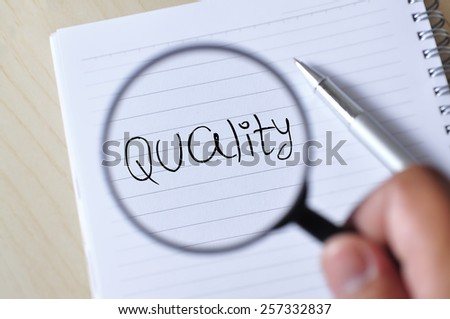 "Hand Holding Magnifying Glass on Note Book with Pen Write ""QUALITY"", Focus on Note Book"
