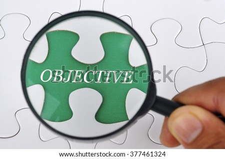 """Hand Holding Magnifying Glass Searching Missing Puzzle Pieces """"OBJECTIVE"""" - stock photo"""