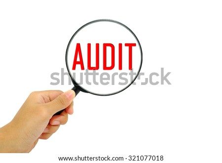 Hand holding magnifying glass with words Audit. - stock photo