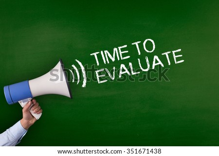 Hand Holding Megaphone with TIME TO EVALUATE Announcement - stock photo