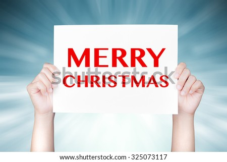 hand holding merry christmas banner on blue abstract background