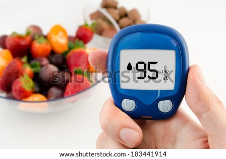 Hand holding meter. Diabetes doing glucose level test. Fruits in background - stock photo