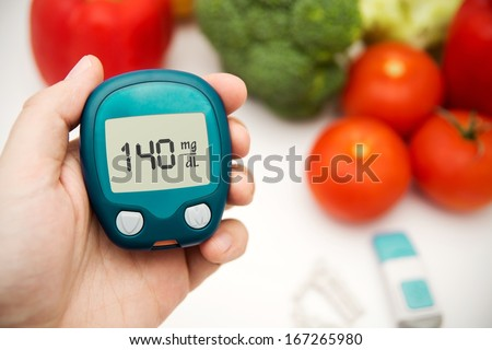 Hand holding meter. Diabetes doing glucose level test. Vegetables in background - stock photo