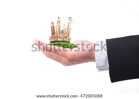 Hand holding miniature building model On white background. Real estate business concept