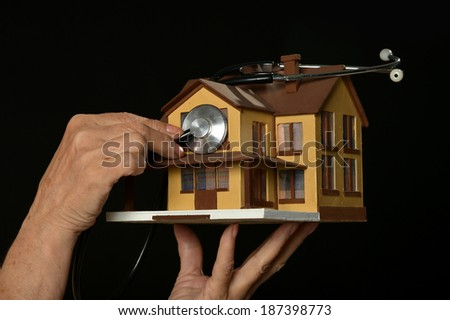 Hand holding miniature house and stethoscope  on black background