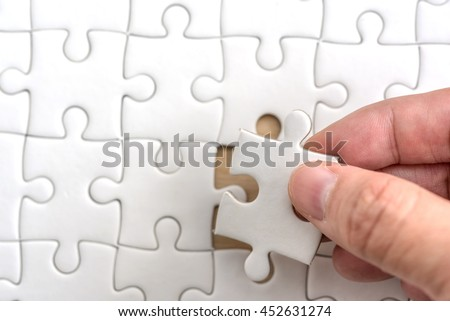 Hand holding missing jigsaw puzzle piece down in to the place, close up