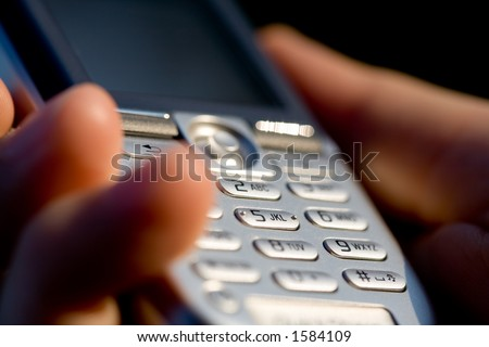 Hand holding mobile phone. Macro shot with shallow depth of field. - stock photo