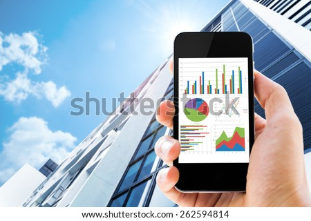hand holding mobile phone with analyzing graph against office buildings with sun - stock photo