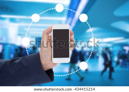Hand holding mobile phone with blur crowd background