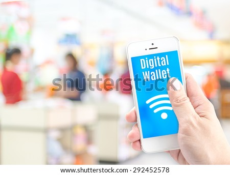 Hand holding mobile phone with digital wallet at supermarket blur background, Digital economy concept. - stock photo