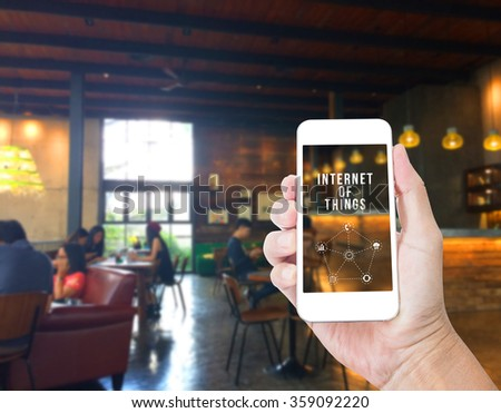 Hand holding mobile phone with Internet of things word with blur coffee shop background,Digital Marketing concept - stock photo