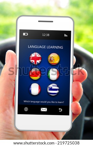 hand holding mobile phone with language learning application in the car - stock photo