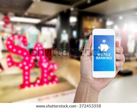 Hand holding mobile phone with mobile banking on screen for E-commerce business concept - stock photo