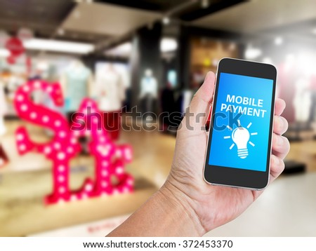 Hand holding mobile phone with mobile payment on screen for E-commerce business concept - stock photo