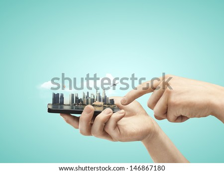 hand holding mobile phone with model city - stock photo