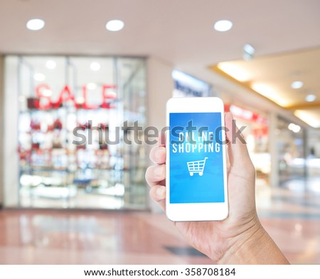 Hand holding mobile phone with Online shopping word with blur shop outlet background,Digital Marketing concept - stock photo