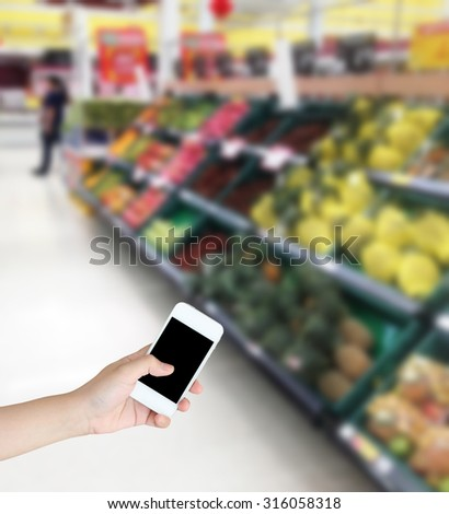 Hand holding mobile phone with Vegetables and fruit on shelf in supermarket blurred background - stock photo