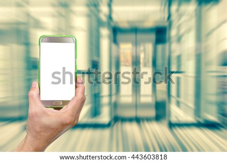 hand holding mobile smart phone with abstract blur elevator background,vintage effect style - stock photo