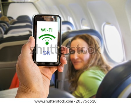 Hand holding mobile smart phone with connect wifi on the airplane - stock photo
