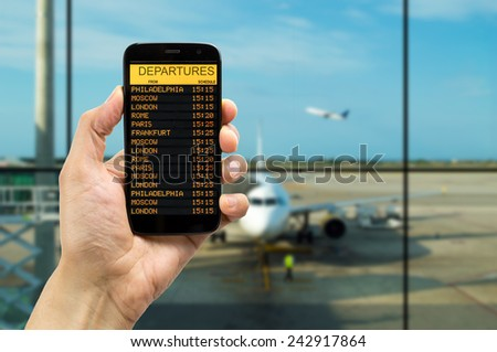 Hand holding mobile smart phone with connect wifi on the airport and see departures board - stock photo