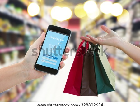 hand holding mobile smart phone with cyber mobile shop  on super market blur background and shopping bags - e-commerce and cyber  retail  marketing concept - stock photo