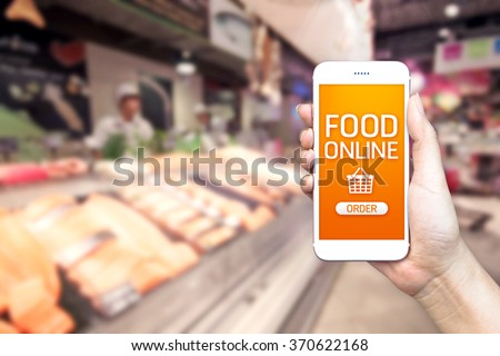 Hand holding mobile with grocery online on screen with blur supermarket background, food online delivery concept. - stock photo