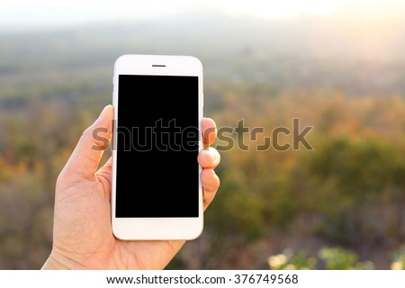 Hand holding mockup smartphone with sunlight and mountain background - stock photo