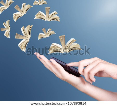 Hand holding modern mobile phone and open books flying away. Education concept - stock photo
