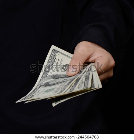 Hand holding money against dark background (concept of bribe/corruption) - stock photo