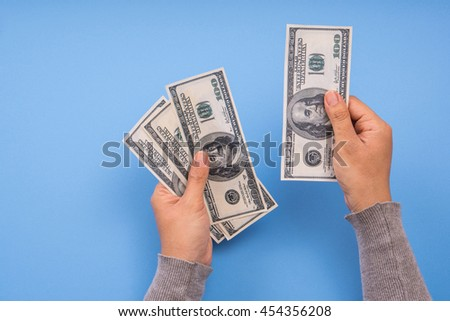 hand holding money and counting, blue background. - stock photo