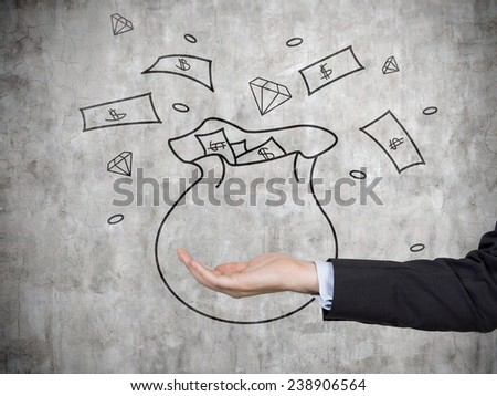 hand holding money bag on gray wall  background - stock photo