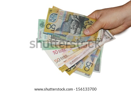 Hand holding multi currency money bills