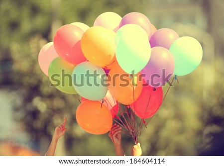 Hand holding multicolored balloons - stock photo