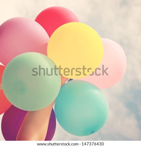 Hand holding multicolored balloons with retro instagram filter effect - stock photo